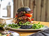 A black bread double burger with bacon, lettuce and cheese on a wooden skewer