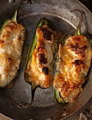 Three stuffed jalapeños in a pan (seen from above)