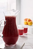 Freshly pressed grapefruit and pomegranate juice in a glass jug