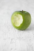 A Granny Smith apple with a bite taken out