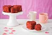 Mini heart-shaped Red Velvet cakes on a plate and a cake stand