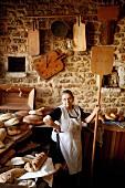 Bäckerin mit Brotschaufel neben Theke mit frischen Brotlaiben in Bäckerei mit rustikaler Natursteinwand