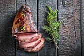 Smoked ham with a sprig of juniper on a scorched tabletop