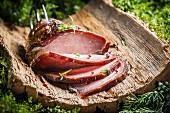 Smoked ham with herbs on a piece of bark