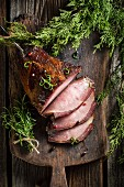 Smoked ham with herbs on a wooden board