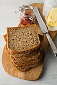 Slices of wholemeal bread stacked on a wooden board with butter and strawberry jam