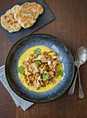Chickpea curry with roasted cauliflower, turmeric yoghurt sauce, almonds and naan bread