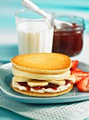 An English muffin with bananas and strawberry jam