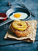 Grilled pork knuckle and pineapple slices with mustard sauce and a fried egg