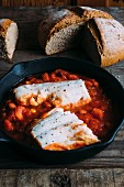 Tomato and bean stew with cod in a cast-iron pan with a loaf of rye bread in the background