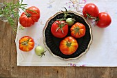 An arrangement of home-grown vine tomatoes on an embroidered tablecloth