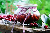 Cherry compote in a jar and fresh cherries on a rustic wooden table