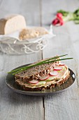 A wholemeal sandwich with ripe cashew nut cheese and radishes (vegan)