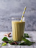 A smoothie made from leaves, oranges, pecan nuts and turmeric