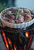 Gegrillte Hühnerschlegel mit Rosmarinzweig in weisser Auflaufform auf Feuerkorb mit Grillgitter
