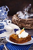 A slice of coconut, walnut and carrot cake with coconut cream and coconut flour sugar for Easter
