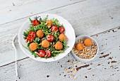 Rocket salad with tomatoes and crispy mozzarella balls