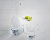A carafe of water and limes