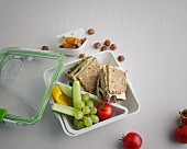 A sandwich, fruit and vegetables in a lunch box