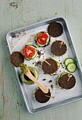 Pumpernickel burgers with pesto, tomatoes and cucumber