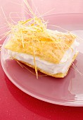 A puff pastry slice with cream and caramel threads
