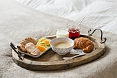 Café au lait, a croissant and fresh fruit on a breakfast tray on a white bed
