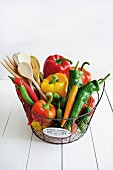 Colourful peppers and a wooden spoon in a wire basket