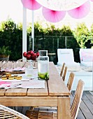 Pink lanterns on summer terrace with wooden table