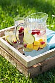 Fruity punch in a wooden crate in a meadow