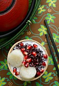 Tape Uli (sweet, fermented, black sticky rice with coconut milk, Indonesia) with pomegranate seeds