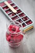 Beeren-Eiswürfel im Eiswürfelformer und in einem Glaskrug
