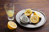 Freshly squeezed lemon juice in a glass with squeezed lemon halves on a metal plate