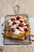 Waffles topped with cream, raspberries and caramel sauce