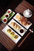 Knusprig frittiertes Hähnchenfleisch mit Erdnusssauce, gebratene Gyoza (Teigtaschen aus Japan) und gefüllte Nudeltaschen mit frittierten Knoblauchscheiben