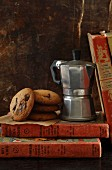 Chocolate chip cookies next to an espresso maker on a pile of old books
