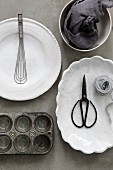 Baking utensils and white crockery on a grey surface