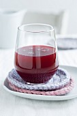 A glass of freshly pressed pomegranate juice on homemade, crocheted coasters