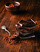 Ein Stapel Schokoladenstücke daneben Kakaopulver