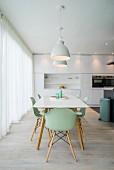 weiße Designerküche mit Essplatz und mintgrünen Schalenstühlen