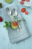 Silver spoons on linen napkin with strawberry tendril, strawberries and lime