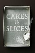 Schriftzug 'Cakes & Slices' aus Puderzucker in Metallbackform