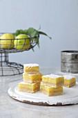 Zitronenschnitten vor Drahtkorb mit Zitronen