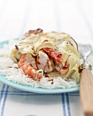 Grilled fish parcel wrapped in cabbage on a bed of rice