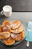 Buttermilk pancakes with icing sugar on a glass plate with a cup of milk