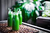 Frische grüne Smoothies in Glasflaschen mit Trinkhalm