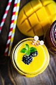 Layered mango and berry smoothie garnished with blackberries
