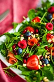 Healthy salad with rocket, spinach, smoked salmon and berries