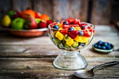 A colourful fruit salad in a jar on rustic wooden surface
