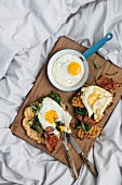 A hearty breakfast with fresh waffles, spinach, bacon and fried eggs