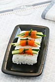 Salmon rolls with cucumber on a bed of rice